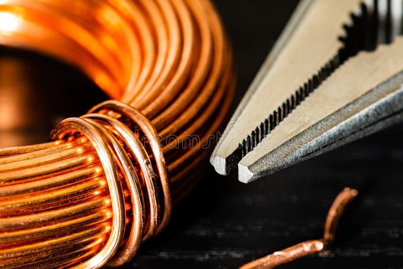 Imagen macra de una bobina del alambre de cobre y de un par de alicates de punta de aguja fotos de archivo