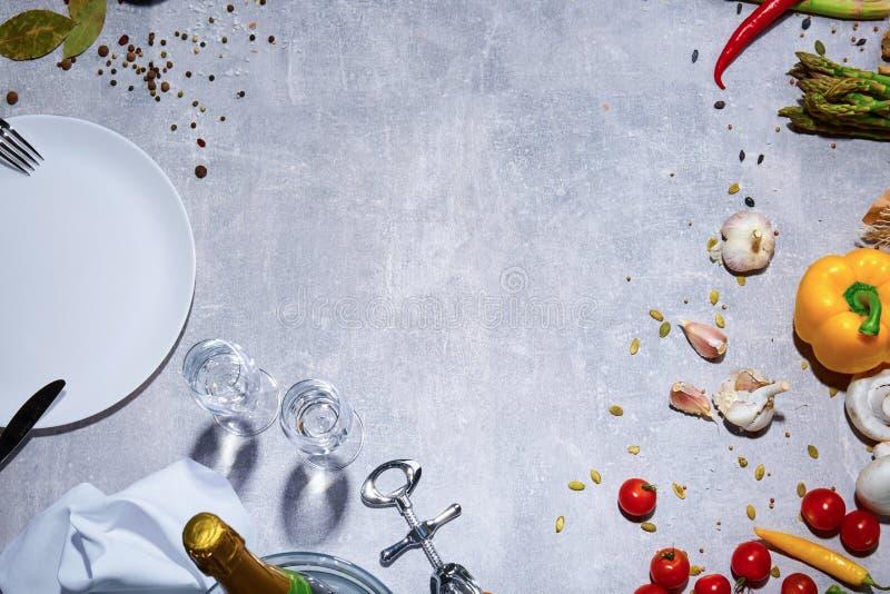 Imagen macra de una composición brillante de la cena en un fondo gris Vajilla al lado de una variedad de verduras coloridas imágenes de archivo libres de regalías