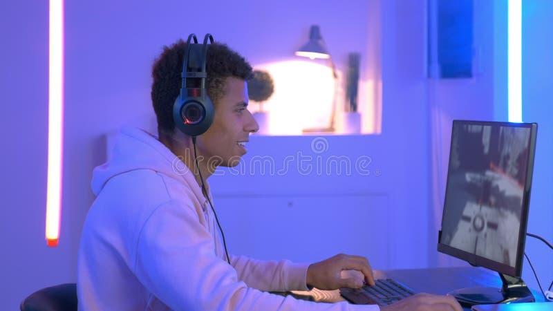 Imagen mediana de un joven jugador negro con auriculares jugando en un tirador en línea foto de archivo