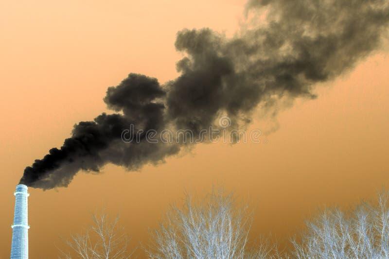 Imagen negativa de un tubo industrial del cual el humo va al cielo sobre los árboles sin follaje Contaminación del concepto del e imagenes de archivo