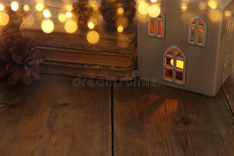 Imagen oscura de la linterna de la casa con la vela ardiente y la luz caliente en las ventanas sobre viejo fondo de madera imagen de archivo
