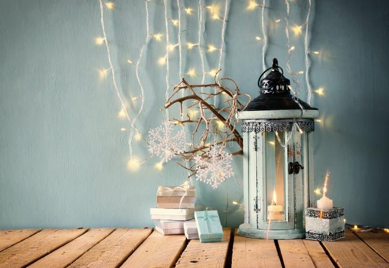 Imagen oscura de la linterna de madera blanca del vintage con los regalos de la Navidad de la vela y las ramas de árbol ardientes imágenes de archivo libres de regalías