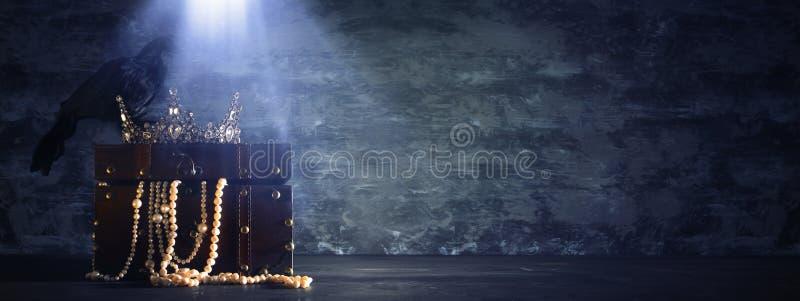 imagen oscura de la reina/de la corona hermosa del rey y del cuervo negro período medieval de la fantasía Foco selectivo fotos de archivo libres de regalías