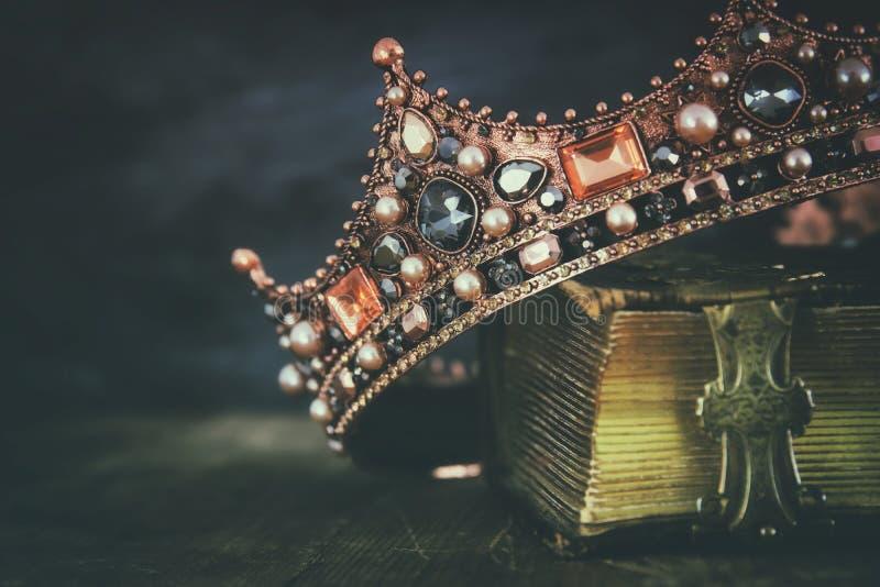 imagen oscura de la reina/de la corona hermosas del rey en el libro viejo imagen de archivo libre de regalías