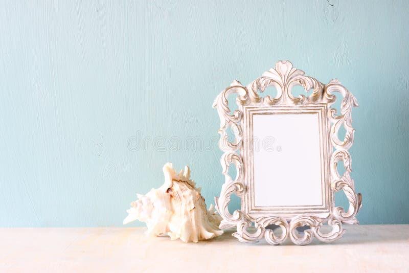Imagen oscura del bastidor y de la concha marina clásicos de la antigüedad del vintage en la tabla de madera Imagen filtrada foto de archivo libre de regalías