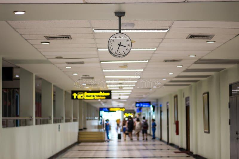 Imagen para su reloj de tiempo del concepto dentro de las imágenes borrosas que viajan del edificio y de la gente del aeropuerto imágenes de archivo libres de regalías