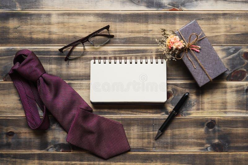 Imagen puesta plana de la caja de regalo, de la corbata, de vidrios y del cuaderno del espacio en blanco r T fotografía de archivo libre de regalías