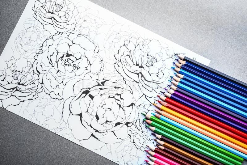 Imagen que colorea y lápices de la tensión anti adulta en la tabla gris, visión superior imagenes de archivo