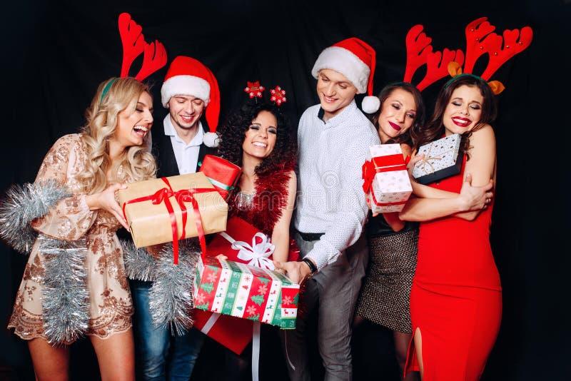 Imagen que muestra al grupo de amigos con los regalos de Navidad Amigos que celebran el partido de la Navidad o de la Noche Vieja fotografía de archivo