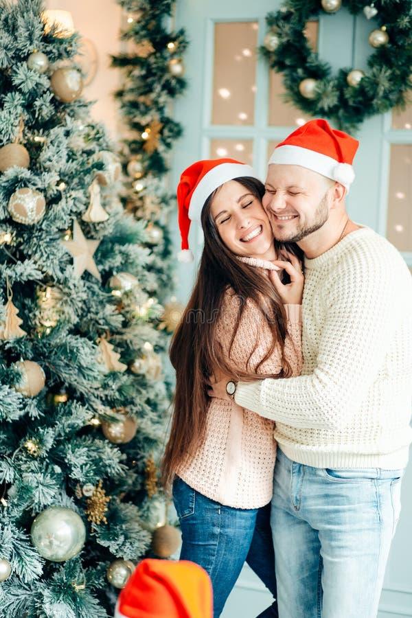 Imagen que muestra los pares jovenes que abrazan sobre el árbol de navidad fotografía de archivo libre de regalías