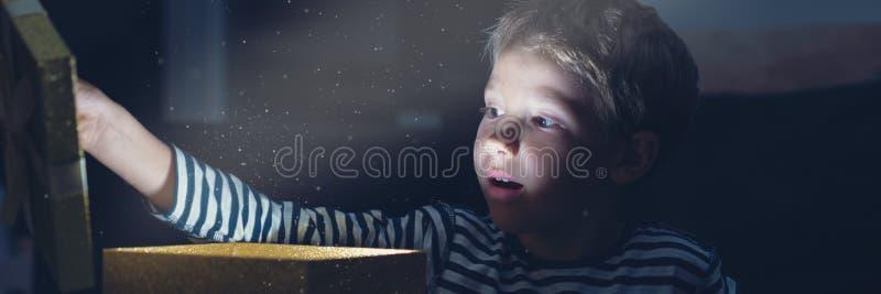 Imagen retra de la visión amplia de un niño pequeño con una expresión sorprendida en su cara como él abre una caja de regalo de o fotografía de archivo