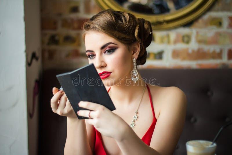 Imagen retra La muchacha pinta su lápiz labial del rojo de los labios imagen de archivo libre de regalías