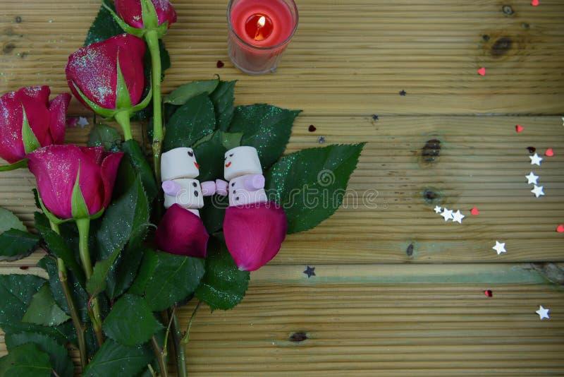 Imagen romántica de la fotografía de la estación del invierno con las rosas rojas y una vela encendida con el muñeco de nieve dur imagen de archivo libre de regalías