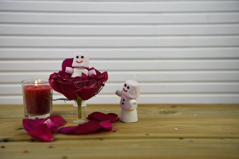 Imagen romántica de la fotografía de la estación del invierno con las rosas rojas y una vela encendida con el muñeco de nieve fel imagen de archivo libre de regalías