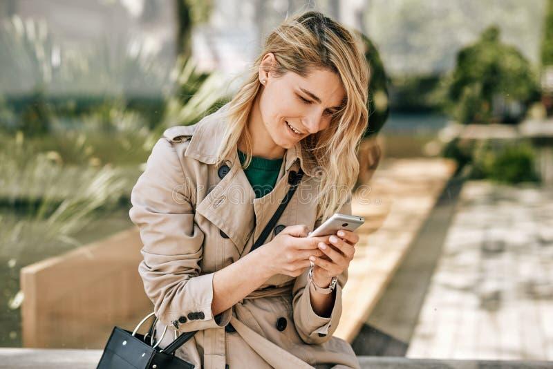 Imagen sincera del aire libre de la mujer hermosa joven que escribe mensajes en el smartphone, el sentarse al aire libre en la ci imágenes de archivo libres de regalías
