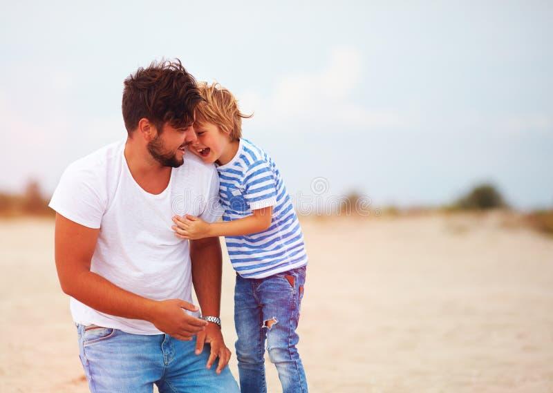Imagen sincera del padre y del hijo que ríen, divirtiéndose junto fotografía de archivo libre de regalías