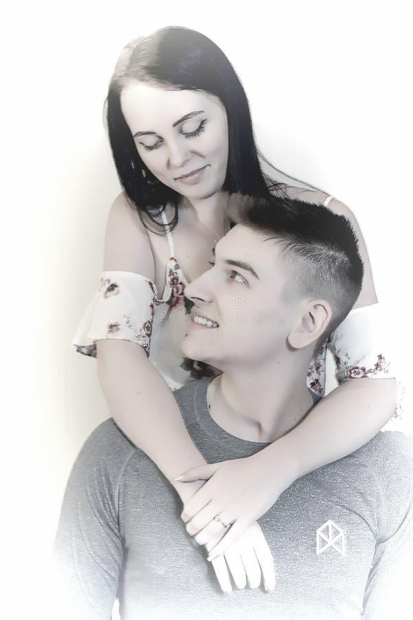 Imagen soñadora de los pares que abrazan con el anillo de compromiso en mano izquierda Aislado en blanco fotos de archivo libres de regalías