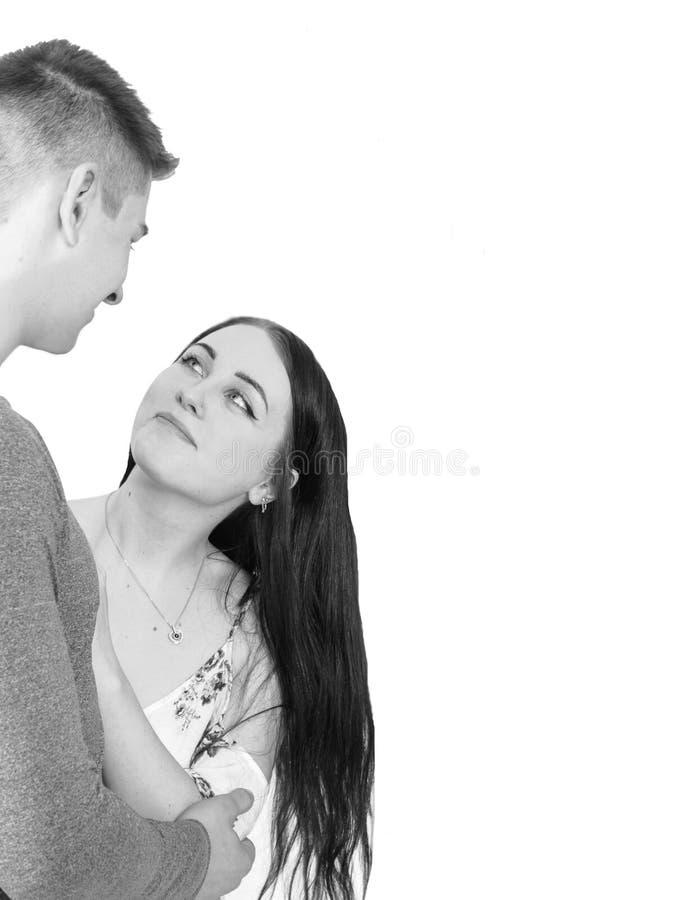 Imagen soñadora de los pares que abrazan con el anillo de compromiso en mano izquierda Aislado en blanco fotos de archivo