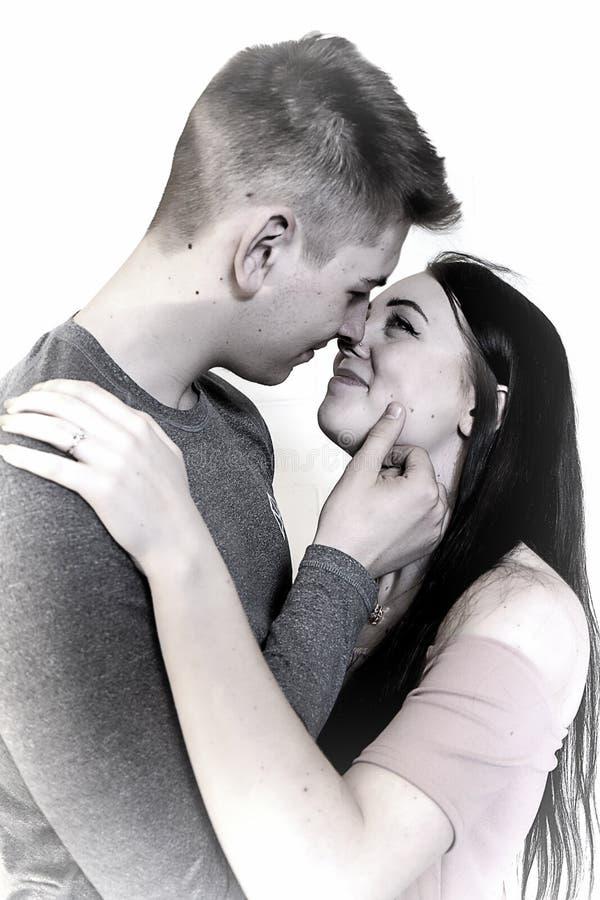 Imagen soñadora de los pares que abrazan con el anillo de compromiso en mano izquierda Aislado en blanco fotografía de archivo libre de regalías