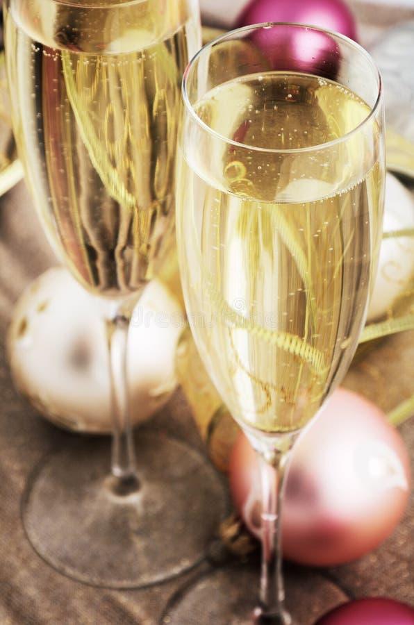 Imagen teñida dos vidrios con champán y la decoración del árbol de navidad imágenes de archivo libres de regalías