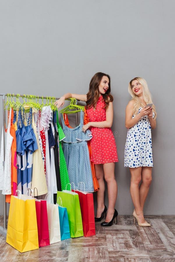 Imagen vertical de dos mujeres que se colocan cerca del estante fotografía de archivo
