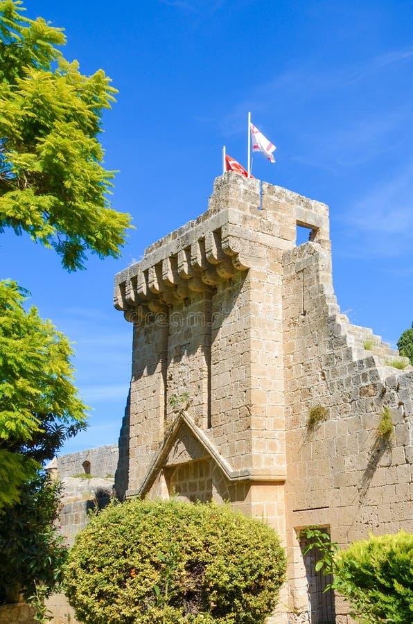 Imagen vertical de la abadía antigua de Bellapais tomada con el parque adyacente y con el cielo azul El monasterio chipriota es u fotografía de archivo libre de regalías