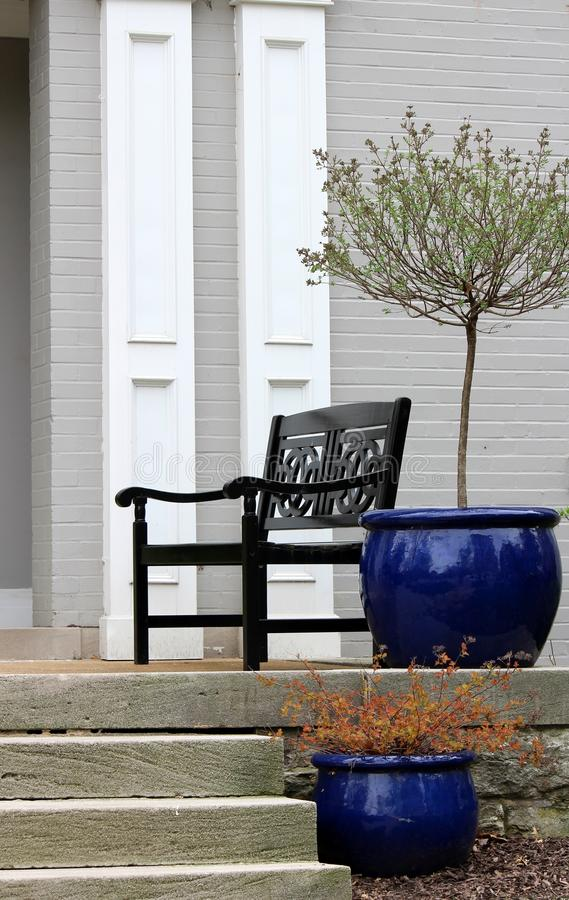 Imagen vertical de la entrada casera con el banco para sentarse y del pote azul brillante con el árbol de florecimiento fotos de archivo