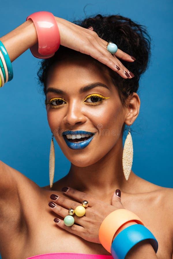 Imagen vertical de la mujer afroamericana de la moda con el cosm colorido imagen de archivo