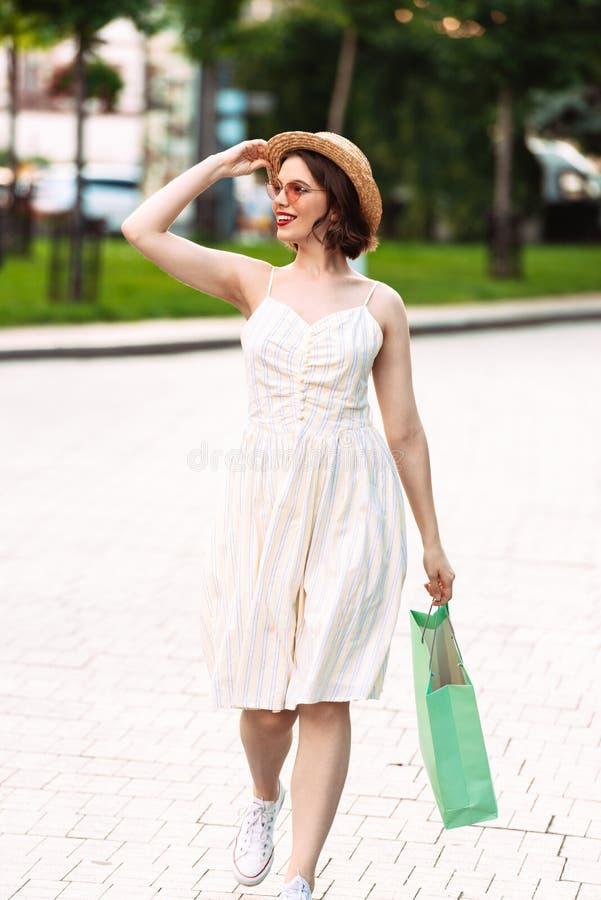 Imagen vertical de la mujer en vestido, sombrero de paja y gafas de sol imágenes de archivo libres de regalías