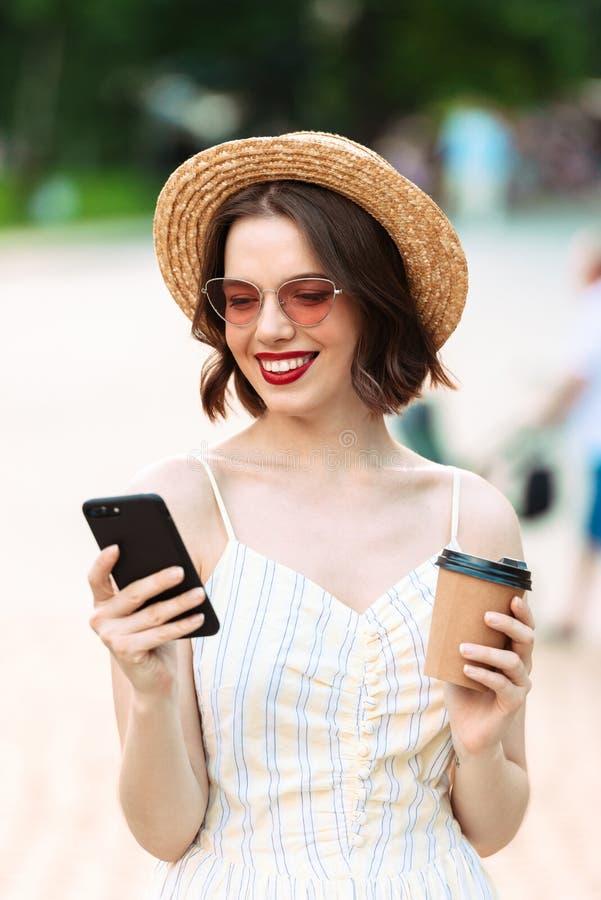 Imagen vertical de la mujer en vestido, sombrero de paja y sunglasse foto de archivo libre de regalías