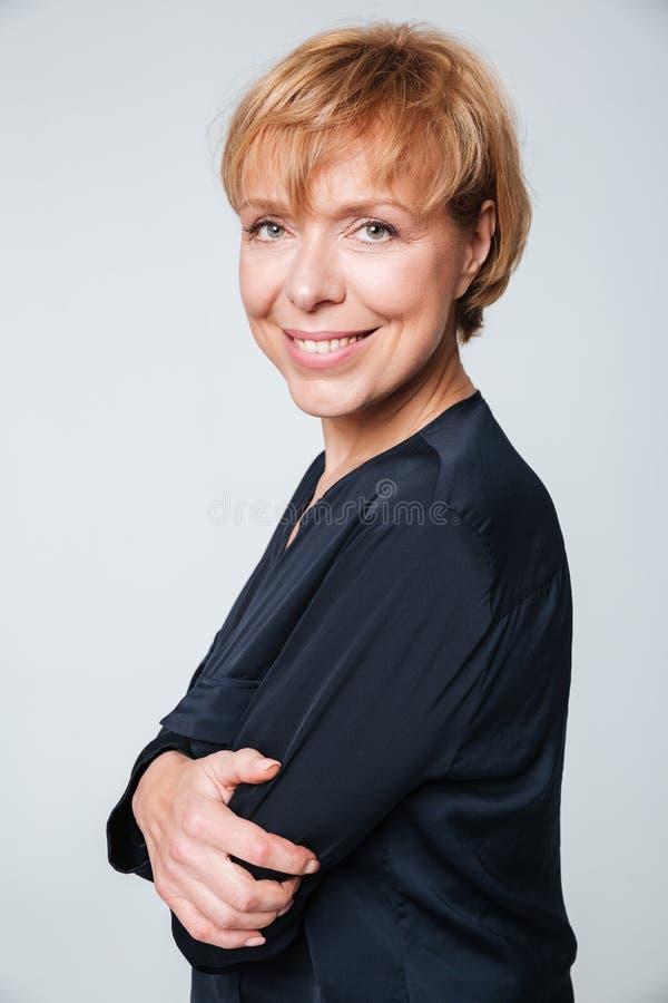 Imagen vertical de la mujer mayor que se coloca de lado foto de archivo