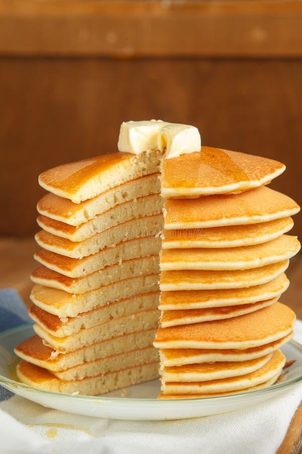 Imagen vertical de la pila del corte de crepe con la miel y la mantequilla encendido foto de archivo