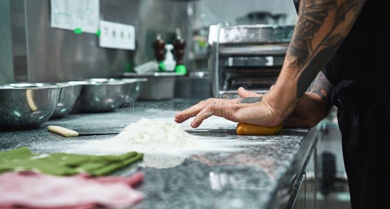 Imagen vertical de las manos del cocinero con los tatuajes que amasan la pasta en cocina del restaurante fotografía de archivo