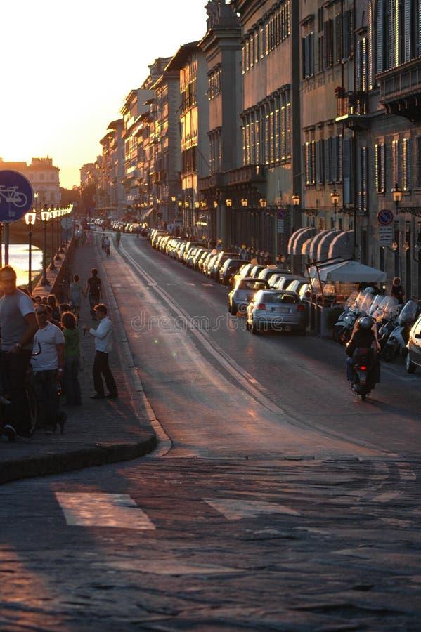 Imagen vertical de una gente en la acera con motocicleta y autos conduciendo por la carretera cerca de los edificios foto de archivo libre de regalías