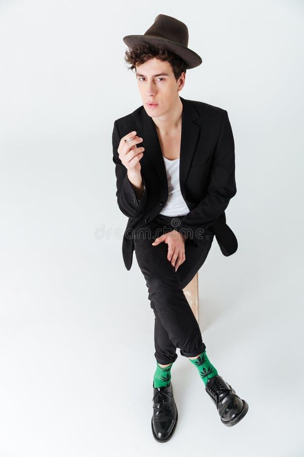 Imagen vertical del hombre en cigarrillo que se sienta y que fuma del traje fotos de archivo