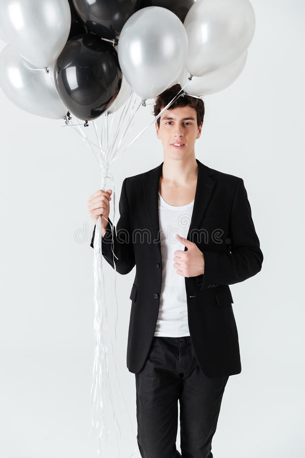 Imagen vertical del hombre sonriente que sostiene los balones de aire foto de archivo libre de regalías