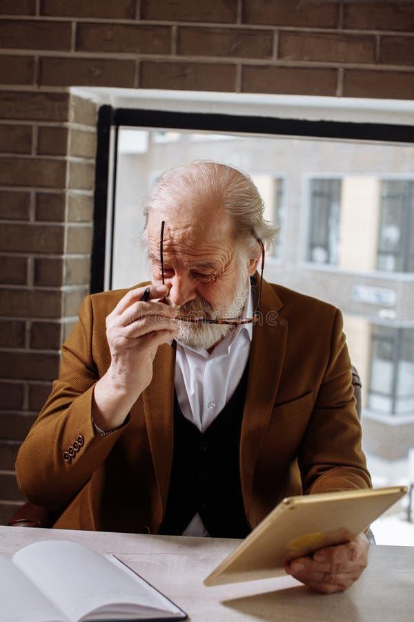 Imagen vertical del jubilado que pone en los vidrios mientras que se sienta en la butaca imagen de archivo libre de regalías
