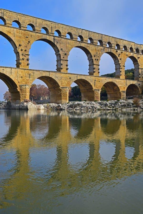 Imagen vertical del nivel de tres arcos de Pont du Gard con la reflexión clara en el río de Gardon imagen de archivo