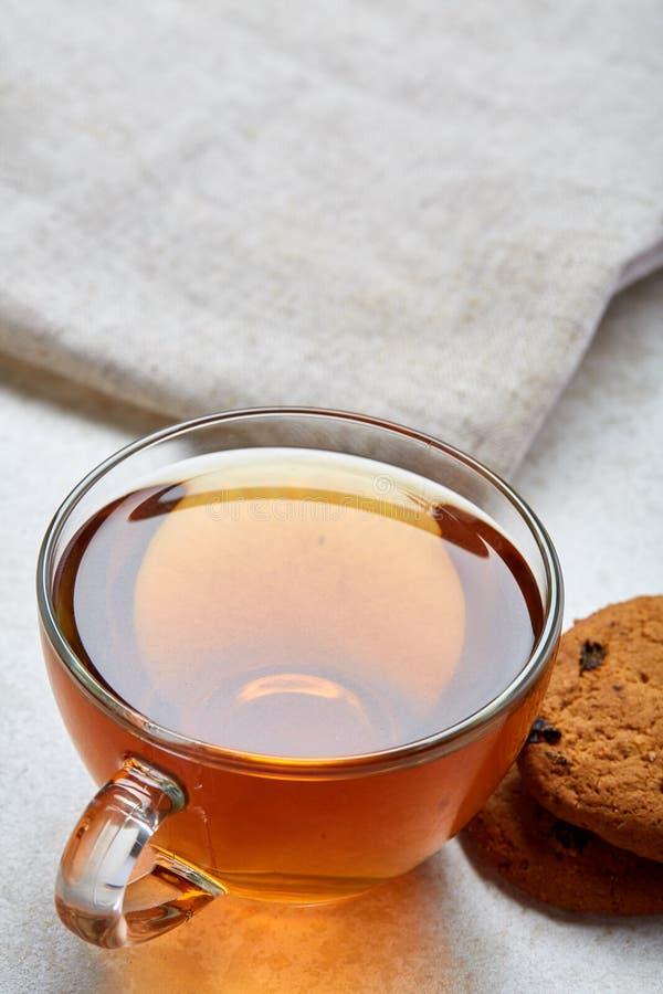 Imagen vertical del primer de la visión superior del té en taza transparente con las galletas y de la servilleta en el fondo blan fotos de archivo