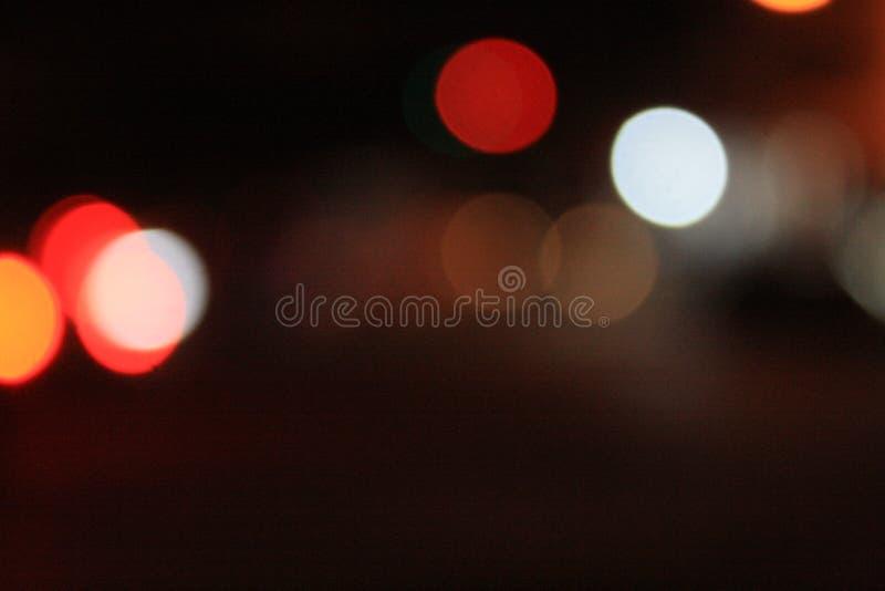 Imagens borradas dos sinais na noite com lotes do bokeh e os círculos e cores coloridas foto de stock