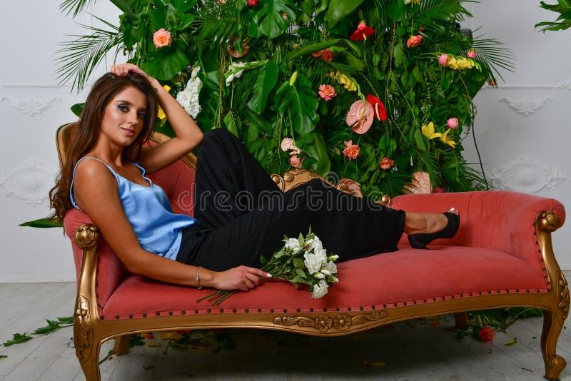 Imagens da menina glamoroso bonita no sofá e na parede vermelhos retros com folhas e as flores verdes imagens de stock