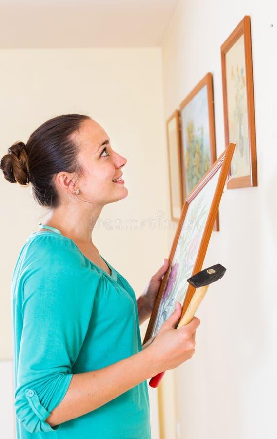 Imagens de suspensão da menina nos quadros na parede na casa fotografia de stock royalty free