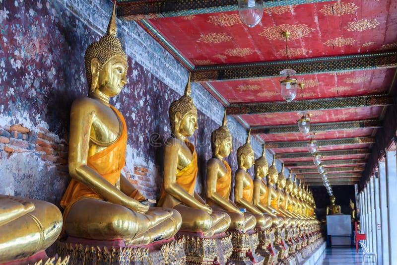 Imagens douradas bonitas da Buda no corredor no templo de Wat Suthat, fotografia de stock