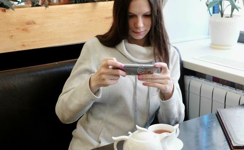 Imagens morenos da jovem mulher do bule e do copo em um café em seu telefone celular Front View imagem de stock royalty free