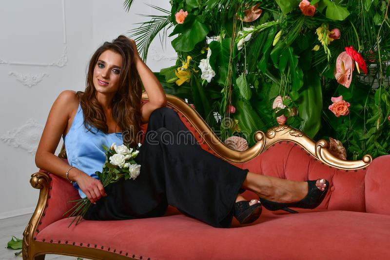 Images of beautiful glamorous girl on the retro red couch and wall with green leaves and flowers stock image