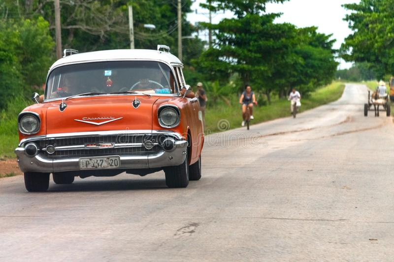 Images of Cuba 2018: Vintage Car. Old vintage car driving in an country road. The land vehicle is an orange colored Chevrolet 1957. There are incidental people royalty free stock photos