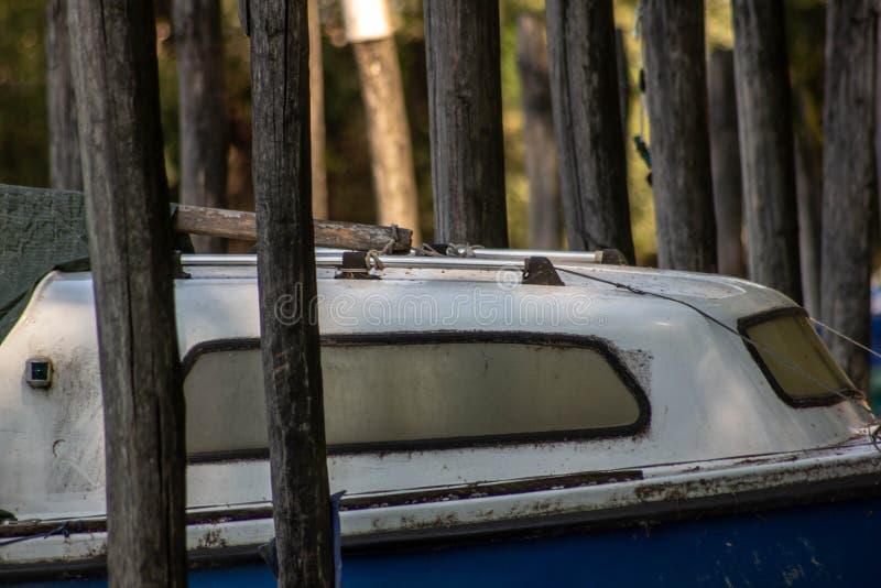 Images de fond qui prennent le détail particulier du petit bateau amarré entre les poteaux sur les banques de la rivière sile images stock