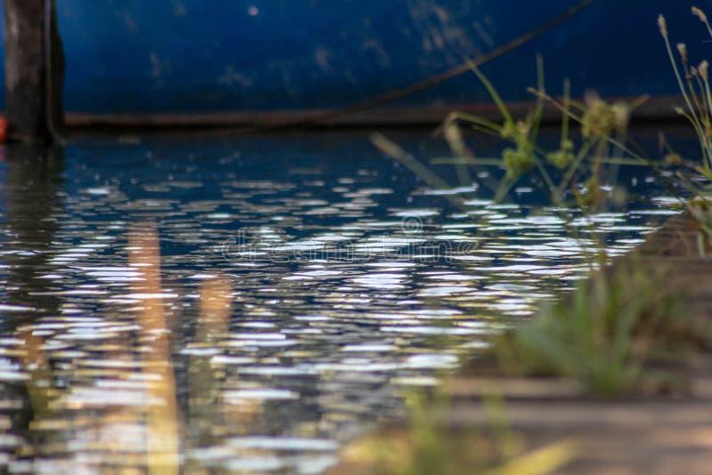 Images de fond qui prennent le détail particulier du petit bateau amarré entre les poteaux sur les banques de la rivière sile photo libre de droits