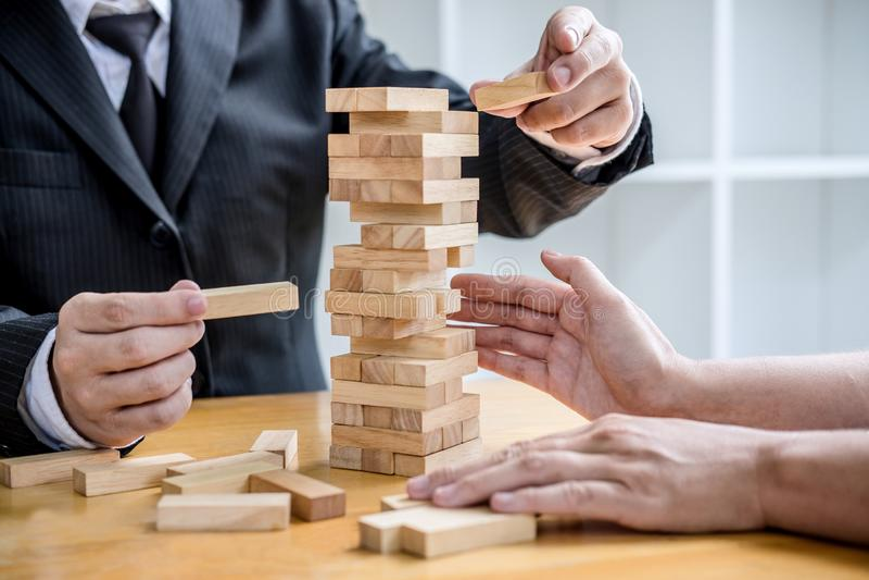 Images de la main des hommes d'affaires pla?ant et tirant le bloc en bois sur la tour, le concept alternatif de risque, le plan e images libres de droits