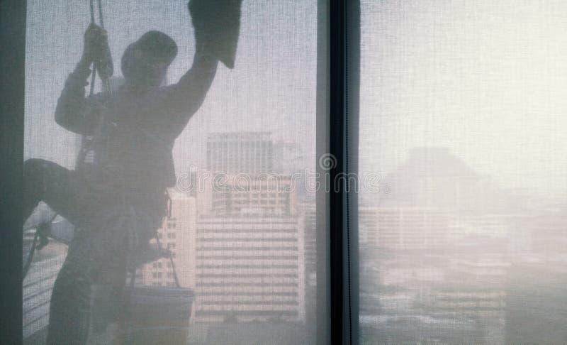 Images de silhouette de l'homme nettoyant l'immeuble de bureaux de fenêtre image libre de droits